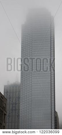 Building in downtown Dallas with low clouds obscuring the top.