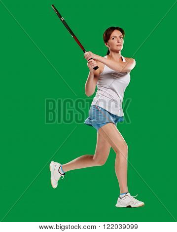 Girl playing tennis, took a picture of a jump, full length. in a green screen studio.Young woman with copy space on green screen chroma key