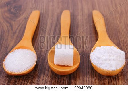 Sugar cube granulated and powdered sugar on wooden spoons ingredient for cooking or baking