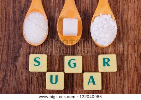 Sugar cube granulated and powdered sugar on wooden spoons with text sugar ingredient for cooking or baking