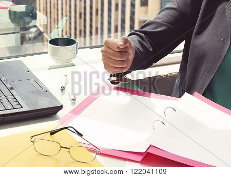 business woman sitting at the desk in office and stamping document