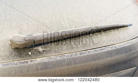 Rear windscreen car window wiper frozen with frost in a cold weather environment.