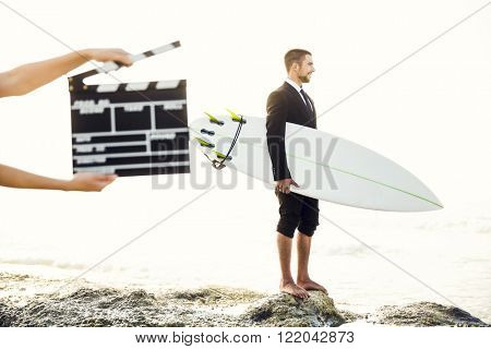 Businessman in front of a clapboard holding is surfboard. Concept about a man starting a new life.