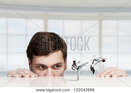 Businessman peeping from under table