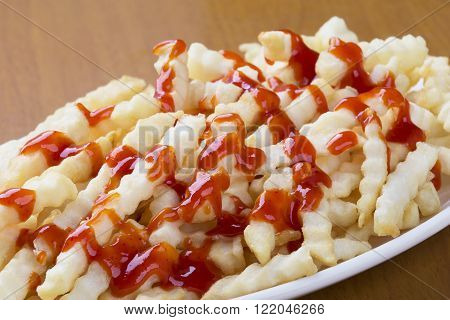 A plate full of delicious crinkle cut style french fries with ketchup