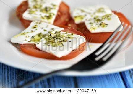closeup of a white ceramic plate with some slices of tomato topped with fresh cheese and dressed with olive oil and oregano, placed on a rustic blue wooden table
