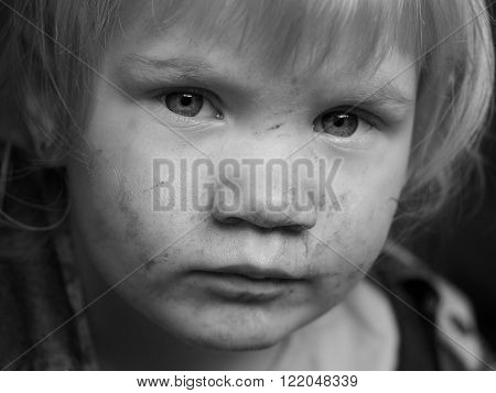 Portrait of a dirty child. The child in the mud smeared face. Black and white