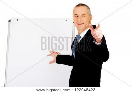 Male executive with marker pointing on someone