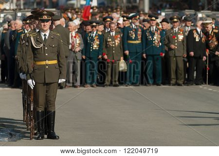 Soldiers of guard of honor at veterans background