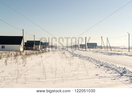 Winter snow covered road leads through a domestic village towards the horizon. Crystal clear blue sky hangs overhead. The worn road has car track and tire imprints. Copy space area for winter travel themed designs.