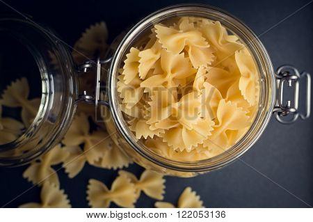 Farfalle pasta in a special jar for food storage, black background