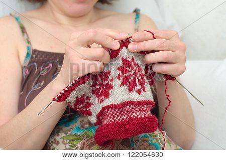 Caucasian woman hands needle knitting snowflake pattern