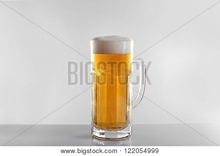 Glass of lager beer on light grey background