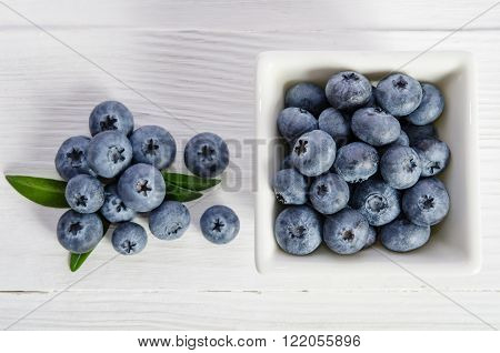 blueberries in a porcelain ramekin and on wooden background