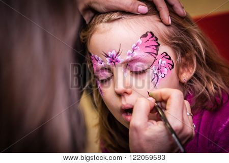 Little girl having her face painted during party