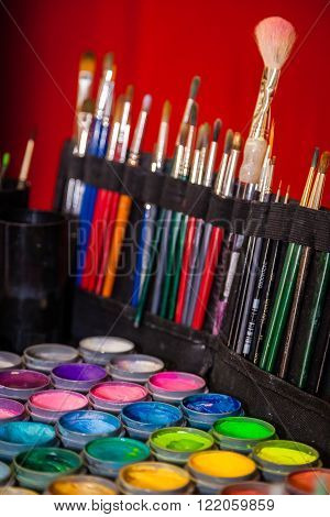 Colorful paint tubes and brushes used for face art painting
