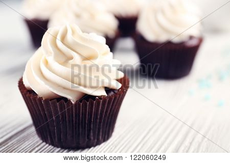 White cupcakes on wooden table