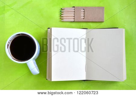 Blank notebook, cup of coffee and crayons on green backround (flat lay) ** Note: Soft Focus at 100%, best at smaller sizes