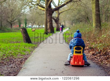 Little boy riding on a plastic car toy on a path in a park in autumn
