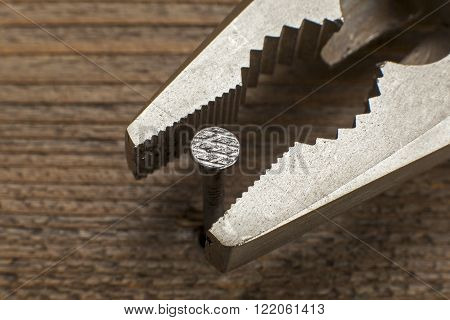 close up view of a nail and a pliers