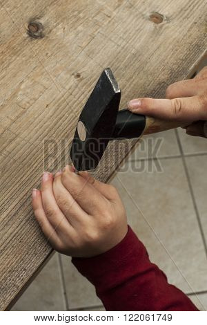 a hammer nail by a worker hit into a wooden plank