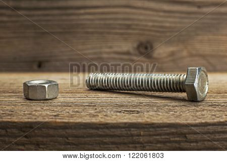 Closeup metal screw bolt and nuts on wooden background.