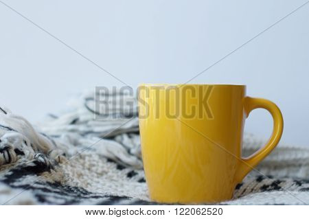 One yellow tea mug on white blanket