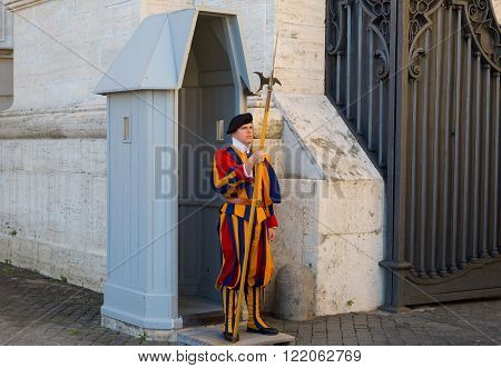 VATICAN CITY - SEPT 22 2015: unidentified Papal Swiss guard standing at the Vatican Museums door in the Vatican. The Swiss guards served since the late 15th century.