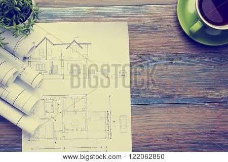 rchitect worplace top view. Architectural project, blueprints, blueprint rolls and  divider compass, calipers on vintage wooden desk table. Construction background. Engineering tools. Copy space.