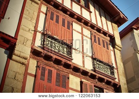Architectural detail of the typical front of historic basque houses in France with the wooden frames and painted louver windows.