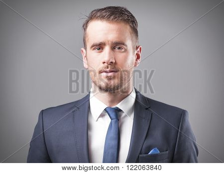 Portrait of a serious businessman on grey background