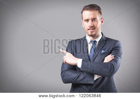 Hnandsome business man pointing at copy space on grey background