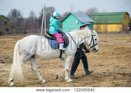 Girl in a turquoise dress sits astride a white horse. The man leads the horse by the reins