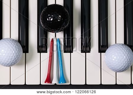 Virtuosic game - Piano keyboard and different golf balls and wooden tees