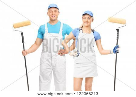 Male and a female decorators holding paint rollers and posing in white uniforms isolated on white background