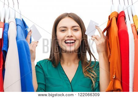 clothing, fashion, sale, shopping and people concept - happy woman showing blank tags on clothes at home wardrobe or shop