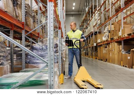 wholesale, logistic, loading, shipment and people concept - man with empty loader and clipboard at warehouse