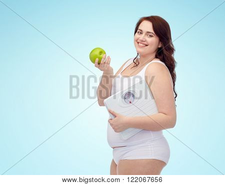 weight loss, diet, slimming, healthy eating and people concept - happy young plus size woman in underwear holding scales and green apple over blue background