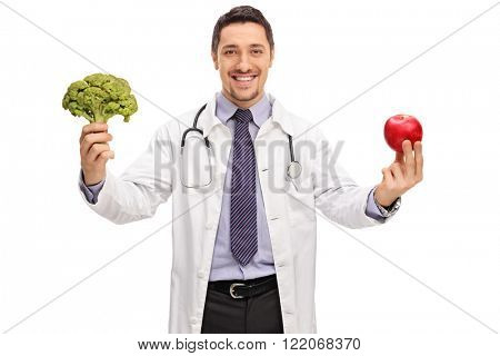 Young cheerful nutritionist holding a piece of broccoli and an apple isolated on white background