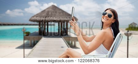 summer vacation, tourism, travel, holidays and people concept - smiling young woman with tablet pc computer sunbathing in lounge or folding chair over bungalow on beach background