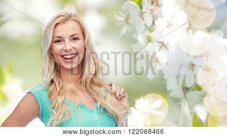 emotions, expressions, hairstyle and people concept - smiling young woman or teenage girl holding her strand of hair over natural spring background