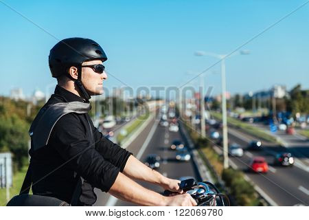 Businessman on electric bicycle driving on bridge