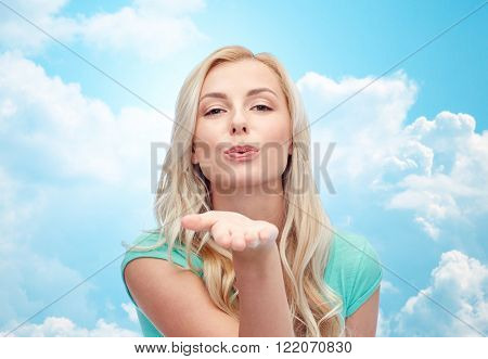 gesture and people concept - smiling young woman or teenage girl sending blow kiss over blue sky and clouds background