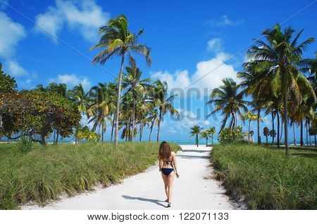 MIAMI BEACH, UNITED STATES - FEBRUARY 4: Girl walk at the sunny Crandon park Beach of Key Biscayne near Atlantic Ocean on 4th of February, 2016 in Miami Beach.