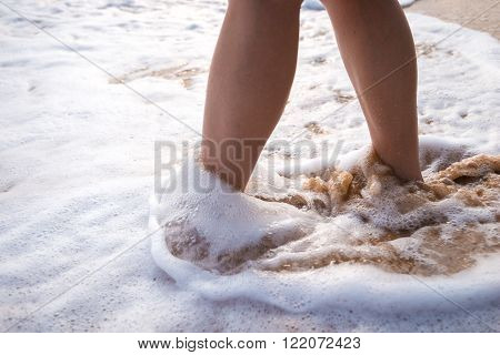 Closeup of a woman's bare feet walking at a beach at sunset, with a wave's edge foaming gently beneath them, toned color