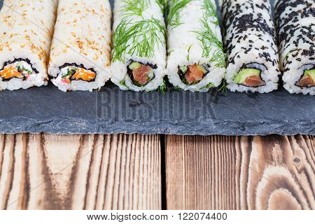 Homemade uramaki sushi rolls on a slate board