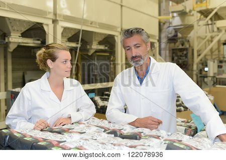 Man and woman looking at packages in factory