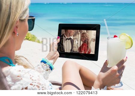 Woman watching movie on tablet computer while lying by the beach