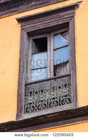 broken window old, yellow building