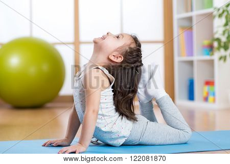 Child girl doing gymnastics on mat at home